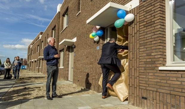 • Directeur-bestuurder Peter van den Heuvel van Woonlinie kijkt toe hoe wethouder Gijs van Leeuwen de eerste woning officieel opent.