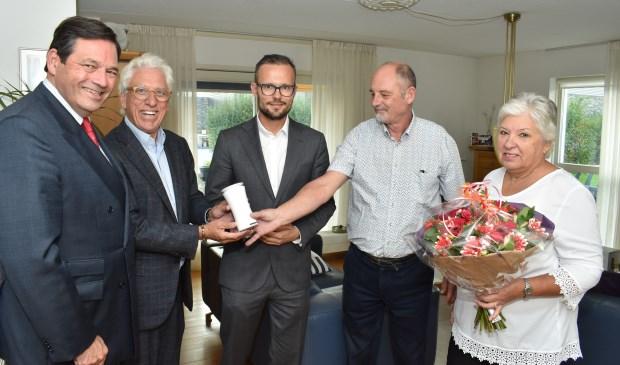 Gedeputeerde Rik Janssen (links) en wethouder Arjan Kraijo (midden) overhandigen de eerste luchtkwaliteitsmeter aan Bram en Lya Hoeijenbos (rechts).