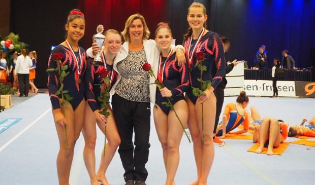 • Het bronzen DOS-team, v.l.n.r. Noa-Mae Blackwell, Margot de Boer, trainster Miranda Deurhof, Danique Meijdam en Eva Bax.