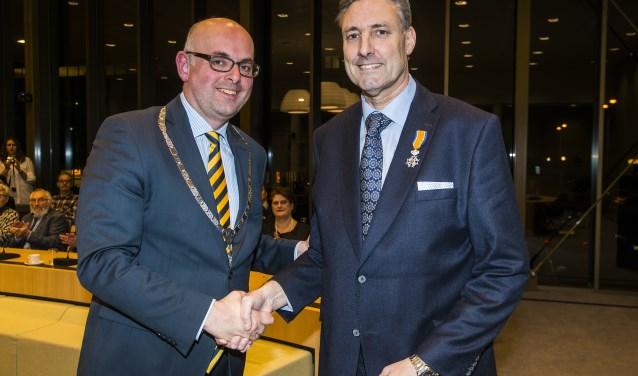 • Burgemeester Martijn Vroom met Hans Butter (rechts), net na de uitreiking van de koninklijke onderscheiding.