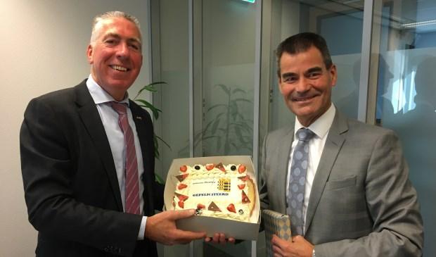 • Burgemeester De Jong van de gemeente Houten overhandigde wethouder Gijs van Leeuwen (l) een taart, voorafgaand aan de collegevergadering van Zaltbommel.