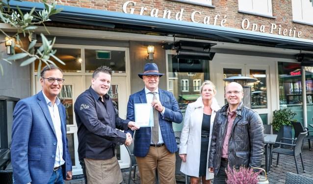 • Burgemeester Henny van Kooten overhandigt het eerste bordje aan Jeroen van Liempt van grand-café Opa Pietje. Links Maarten Mulder.