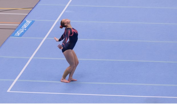 • Sanne Oost tijdens haar gracieus uitgevoerde vloeroefening.