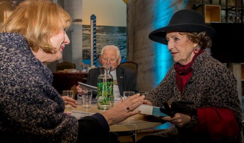 • Teuntje de Haan (links) overhandigt aan Prinses Margriet een exemplaar van haar boek.