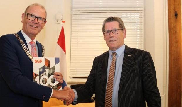 • • Het eerste exemplaar van de SGP-glossy werd uitgereikt aan burgemeester Wim Groeneweg.