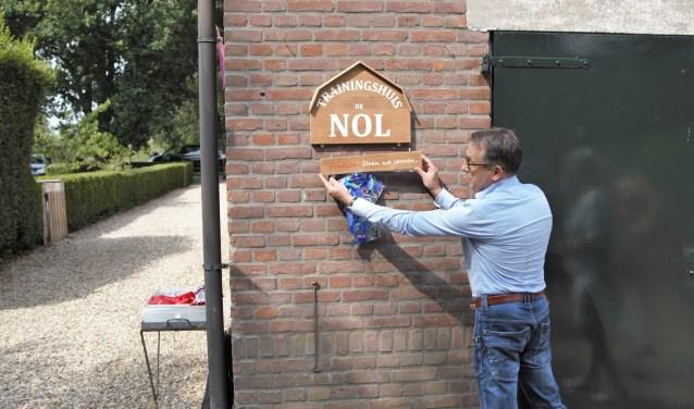 • Bestuurder Harry Vogelaar bevestigt het naambord bij de officiele opening van Trainingshuis De Nol.