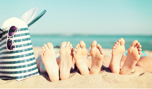 summer vacation, sunbathing and pedicure concept - three women lying on the beach with straw hat, sunglasses and bag