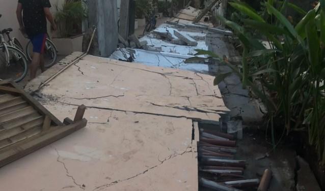 • De omgevallen muur achter het hotel van Ruud en Merel.