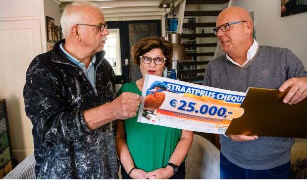 Jan Willem en zijn vrouw uit Ameide worden verrast door Postcode Loterij-ambassadeur Gaston Starreveld met de PostcodeStraatprijs-cheque