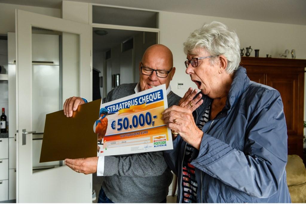 Bep uit Ameide wordt verrast door Postcode Loterij-ambassadeur Gaston Starreveld met de PostcodeStraatprijs-cheque. Foto: Roy Beusker © Alblasserwaard