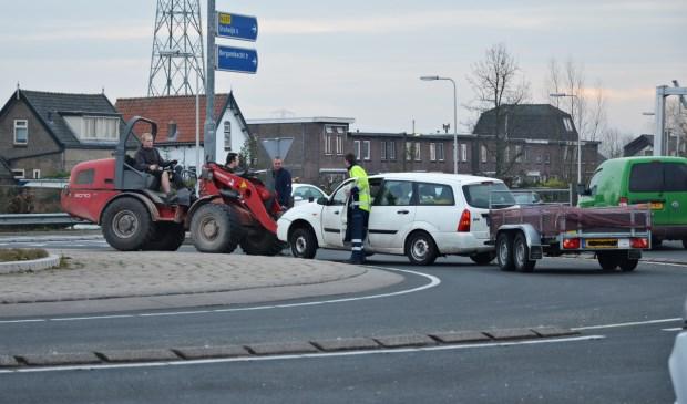 • Een van de voertuigen wordt door een shovel weggehaald.