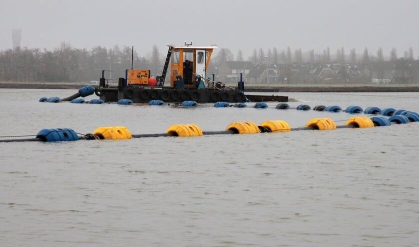 • Het zand voor de bodem gaat via pijpen naar een bootje. Van daaruit wordt het geleidelijk in de surfplas gesproeid.