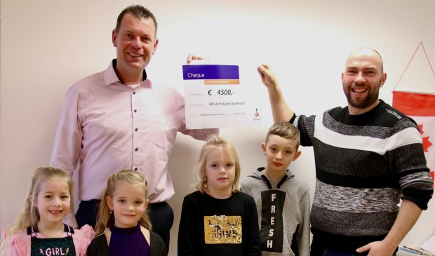 • Stephan van Velduizen (Rabobank Krimpenerwaard) overhandigt de cheque aan Bram de Jong. De kinderen op de foto zijn v.l.n.r.: Joney, Viënne, Karlijn en Marius.
