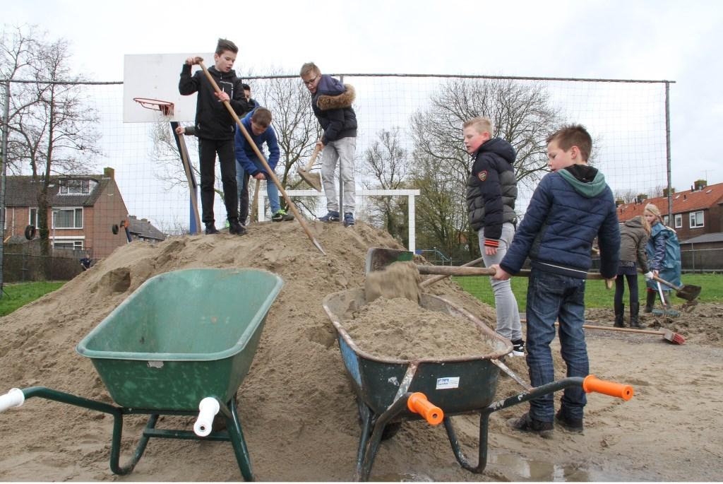 • Ondanks de harde wind werkten de jongens ijverig door. Foto: Anne Marie Hoekstra © Alblasserwaard