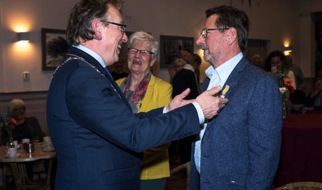 • Burgemeester Keereweer speldt de Koninklijke Onderscheiding op.