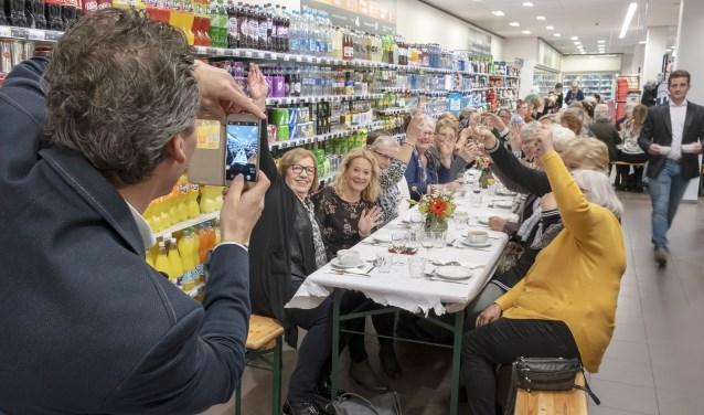 • Supermarkteigenaar Erik Wiersma van de Albert Heijn in Krimpen aan de Lek neemt een foto van de gasten die hun eten kregen geserveerd aan een lange eettafel.