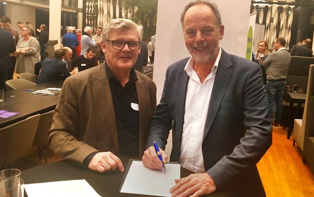 • Cambium-conrector Luuk van Bussel (links) en Adriaan van Beek van Koudetechniek De Laat ondertekenen op een startbijeenkomst in hun samenwerking. Foto: Gerrit Groeneveld © Bommelerwaard