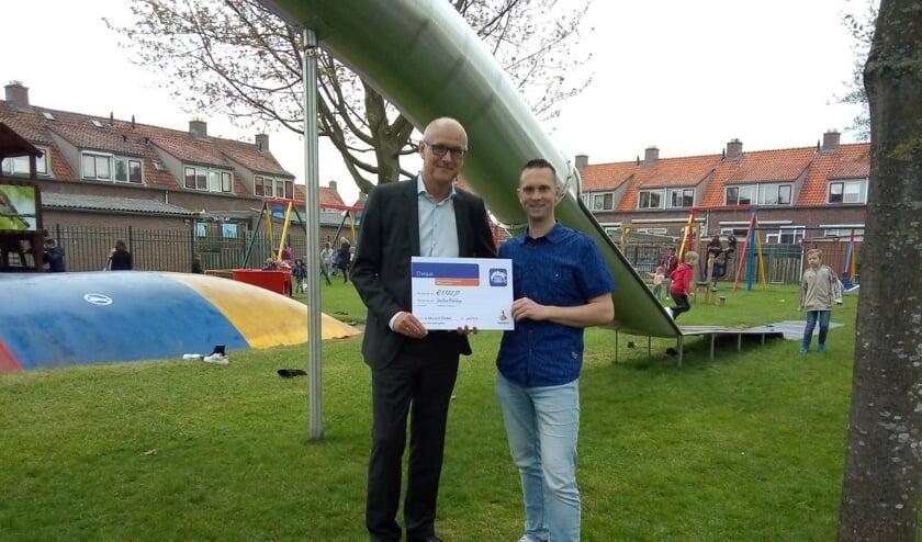 • De heer Spijk (links) overhandigt de cheque aan Pleun Meerkerk.