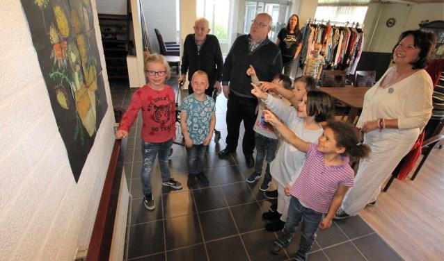 • Leerlingen van obs Het Schateiland laten bewoners van De Breeje Hendrick hun kunstwerken zien.