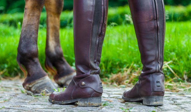 a horsewoman in riding boots near a horse