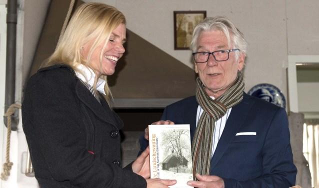 Paula Jorritsma krijgt uit handen van Bert van Straten het eerste exemplaar van 'De Landschewoning'.