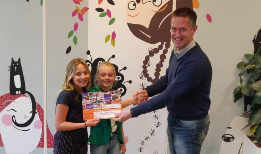 • Interim-directeur Rogier Levy overhandigt de cheque aan de initiatiefneemsters van de sponsorloop, Roos en Sophie.