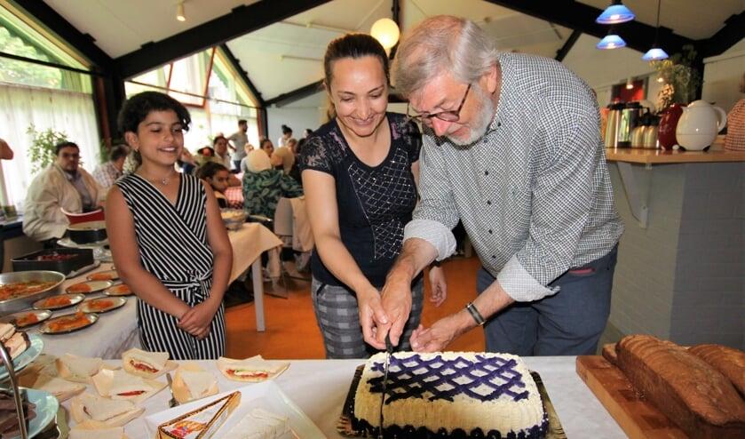 • Henk van der Sijden snijdt de taart aan tijdens het 'bedankfeestje' dat voor hem was georganiseerd.