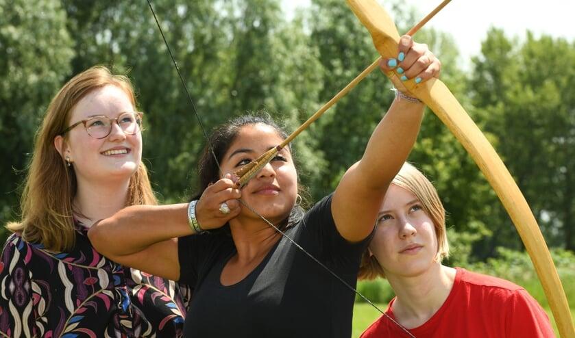 Louise, Gabriela en Romy (vlnr) richten hun pijlen.