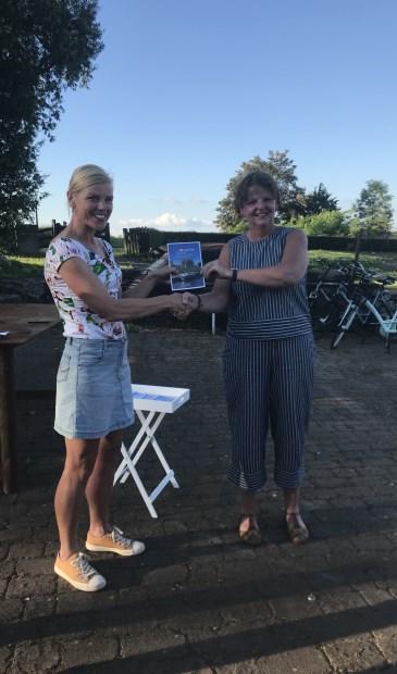 Wethouder Paula Jorritsma krijgt het eerste boekje 'Woudrichem Stroomt' uit handen van Daphne van Hekken van VVV Altena Biesbosch.