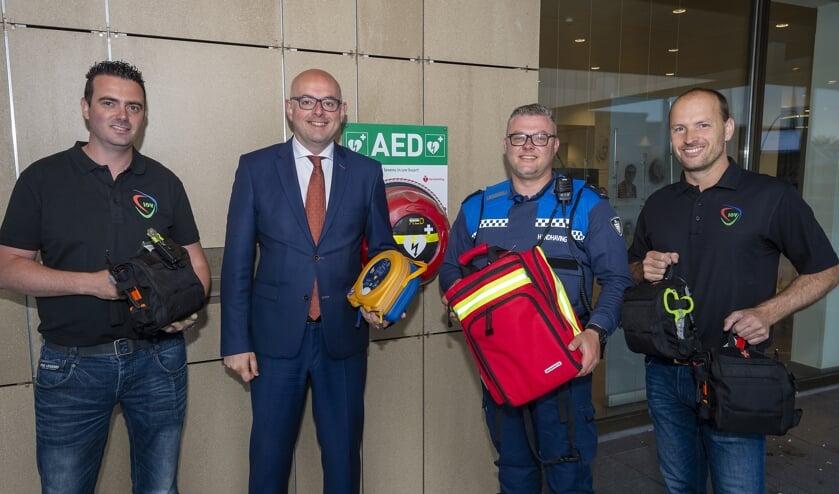 • V.l.n.r.: Marcel Beekman (IOV), Burgemeester Vroom, BOA Xander en Mark Schileroord (IOV). BOA Xander neemt de AED en trauma- en EHBO-pakket in ontvangst.