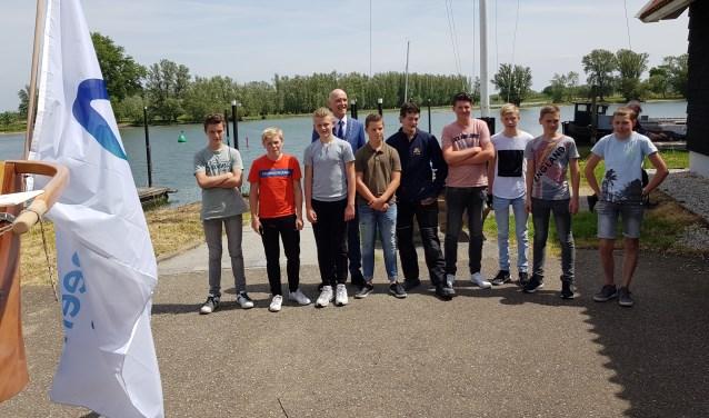 De groep roeiers van het Willem van Oranje College voor hun vertrek, samen met burgemeester Marcel Fränzel.