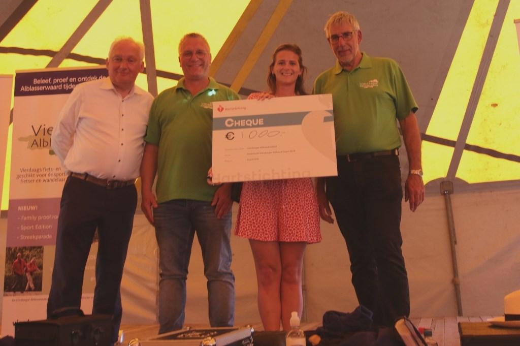 • Burgemeester Van der Borg overhandigt de cheque van 1000 euro aan de Hartstichting. Foto: Joke Snoek © Alblasserwaard
