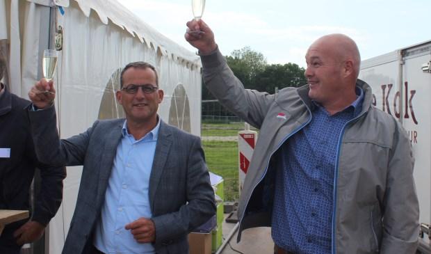 • Wethouder Johan Quik en ontwikkelaar Erik Batenburg (rechts) heffen het glas.   © Alblasserwaard