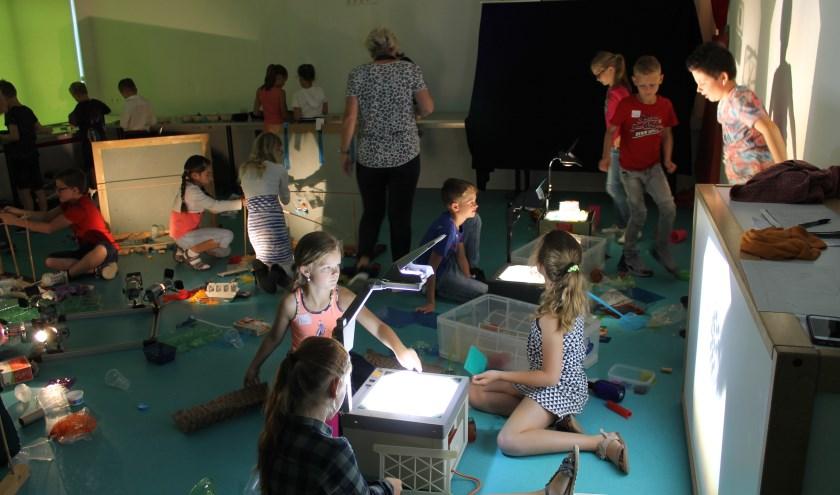 Kinderen aan het werk in het atelier.