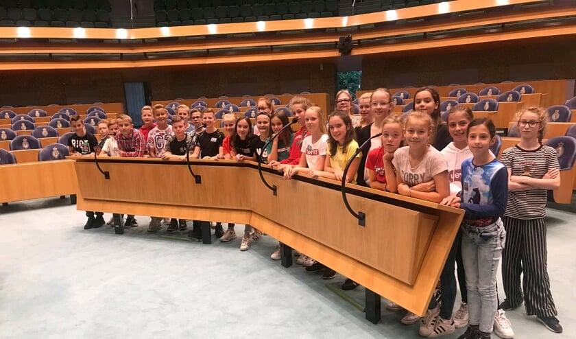 Groep 8 poseert voor de interruptiemicrofoons in de Tweede Kamer.