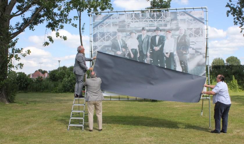 • Jan-Hein de Vreede onthult het laatste doek, geholpen door burgemeester Henny van Kooten en de vader van de fotograaf.