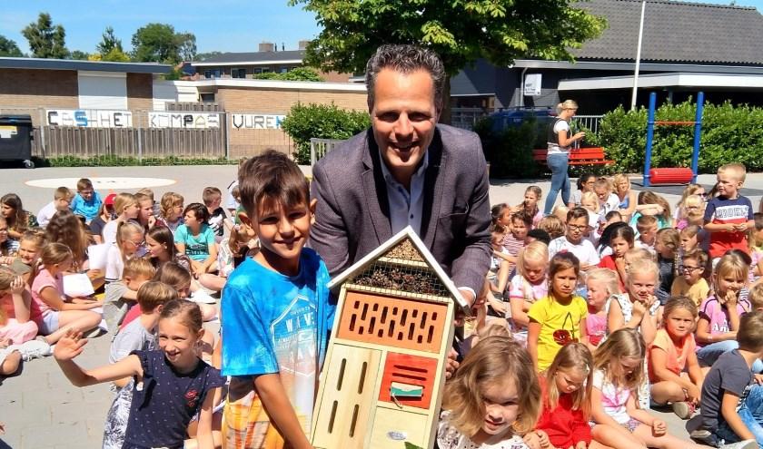 Rutger van Stappershoef overhandigt het insectenhotel aan de jongste en oudste leerling van CBS Het Kompas.
