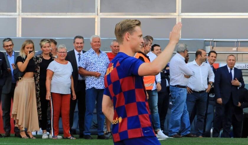 • Frenkie zwaait naar het publiek in Camp Nou; op de achtergrond pinkt zijn familie een traantje weg.
