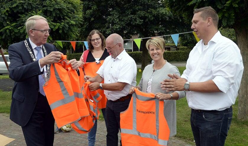 Arie Noordergraaf, de laatste burgemeester van Woudrichem, deelt hesjes uit aan het buurtpreventieteam in Andel, dat in 2017 is opgericht.