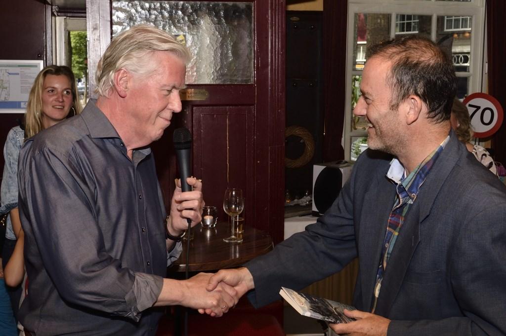 Stan Mooij overhandigd zijn dichtbundel aan wethouder Kees Vortman (rechts)  | Fotonummer: d8f2b6