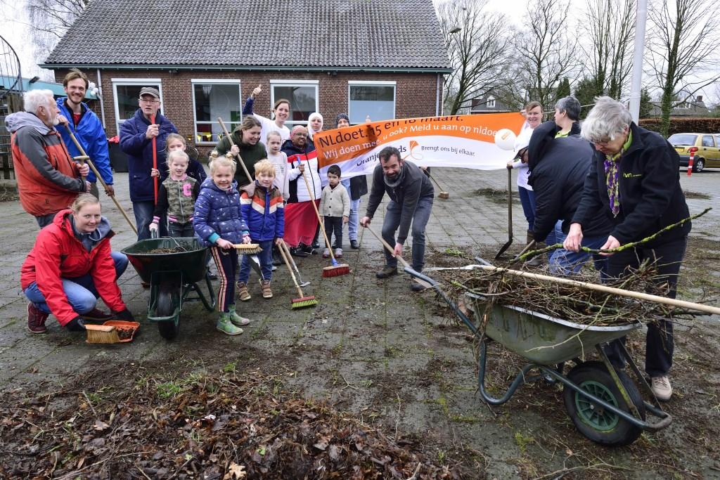 Jong en oud helpen mee om de buitenplein op te ruimen Foto: Wil Feijen © DeMooiSonenBreugelKrant