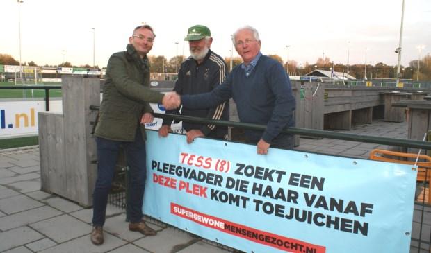 Het is de week van de pleegzorg en bij V'97 hangt dit spandoek. Wethouder Mol, Rinus van der Berg en Piet Dubbeling hingen het woensdag op. Foto: VSK