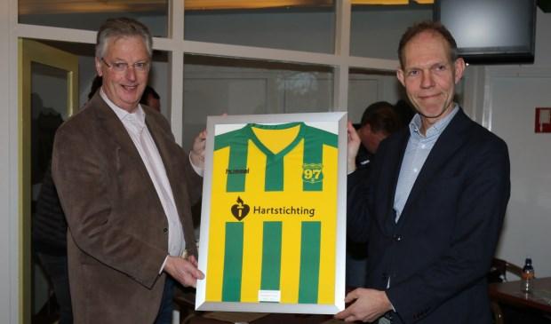 Floris Italianer (r) ontvangt van Ton van Emmerik een ingelijst shirt van de zaterdagselectie met de naam van de Hartstichting. Foto: PR