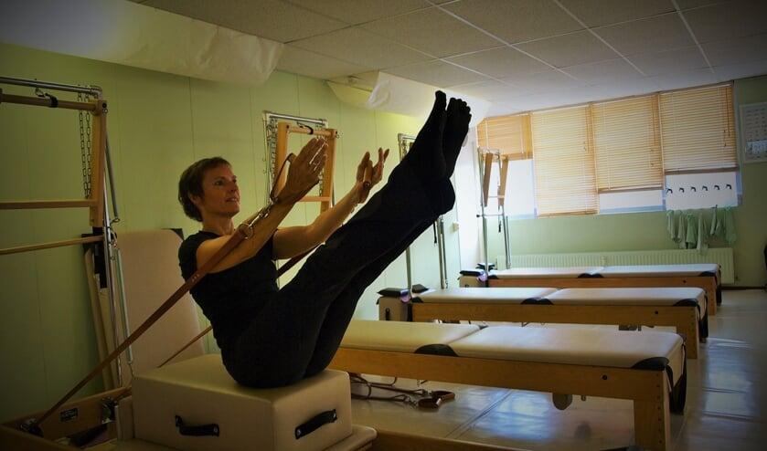 Sylvia Temmink demonstreert een pilates oefening op de Peak Pilates trainingsbank. Foto: Vsk