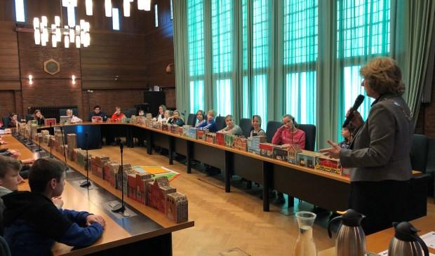 Hoe werkt de politiek en democratie in Nederland? Dat legde burgemeester Bouvy-Koene uit in de raadszaal tijdens een les aan leerlingen van groep 7 en 9. Foto: gemeente Voorschoten