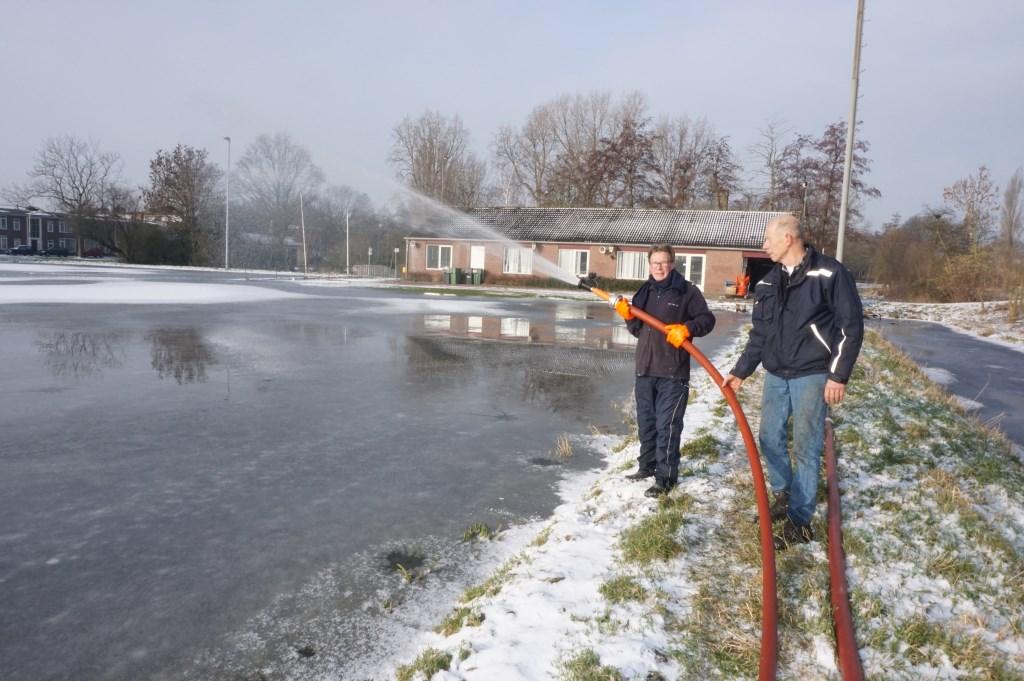 Met man en macht wordt gewerkt aan het ijs van de natuurijsbaan. Foto's: VSK