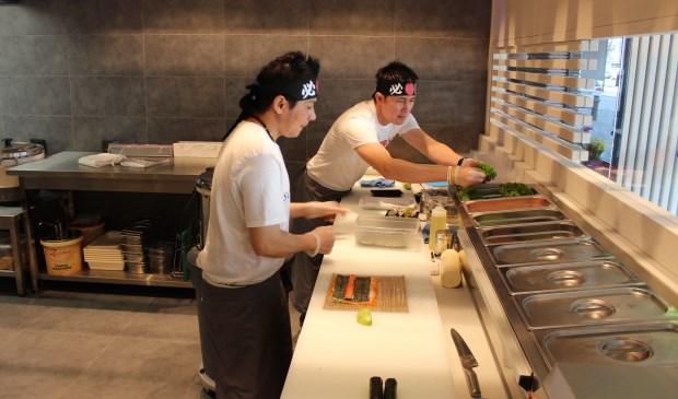 De koks aan het werk in de open keuken.