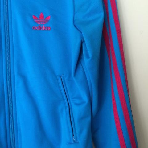 ba659a85e0f Adidas Originals vest in blauw met fuchsia. Heeft 2 zakken met ritsen.  Heeft beschadiging aan de rechtermouw (zie foto)