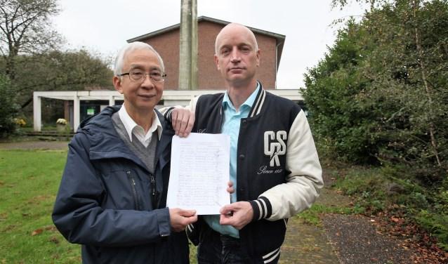 Hans van Ierland enTik Ong tonen de lijsten met handtekeningen van buurtbewoners (tekst: Inge Koot/foto: Peter van Zetten).