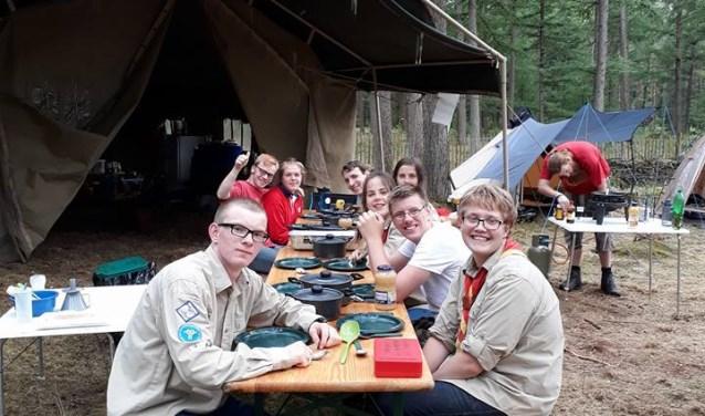 De vrijbuiters van Scouting JMC zitten klaar voor de maaltijd nadat ze zelf gekookt hebben. Foto: pr
